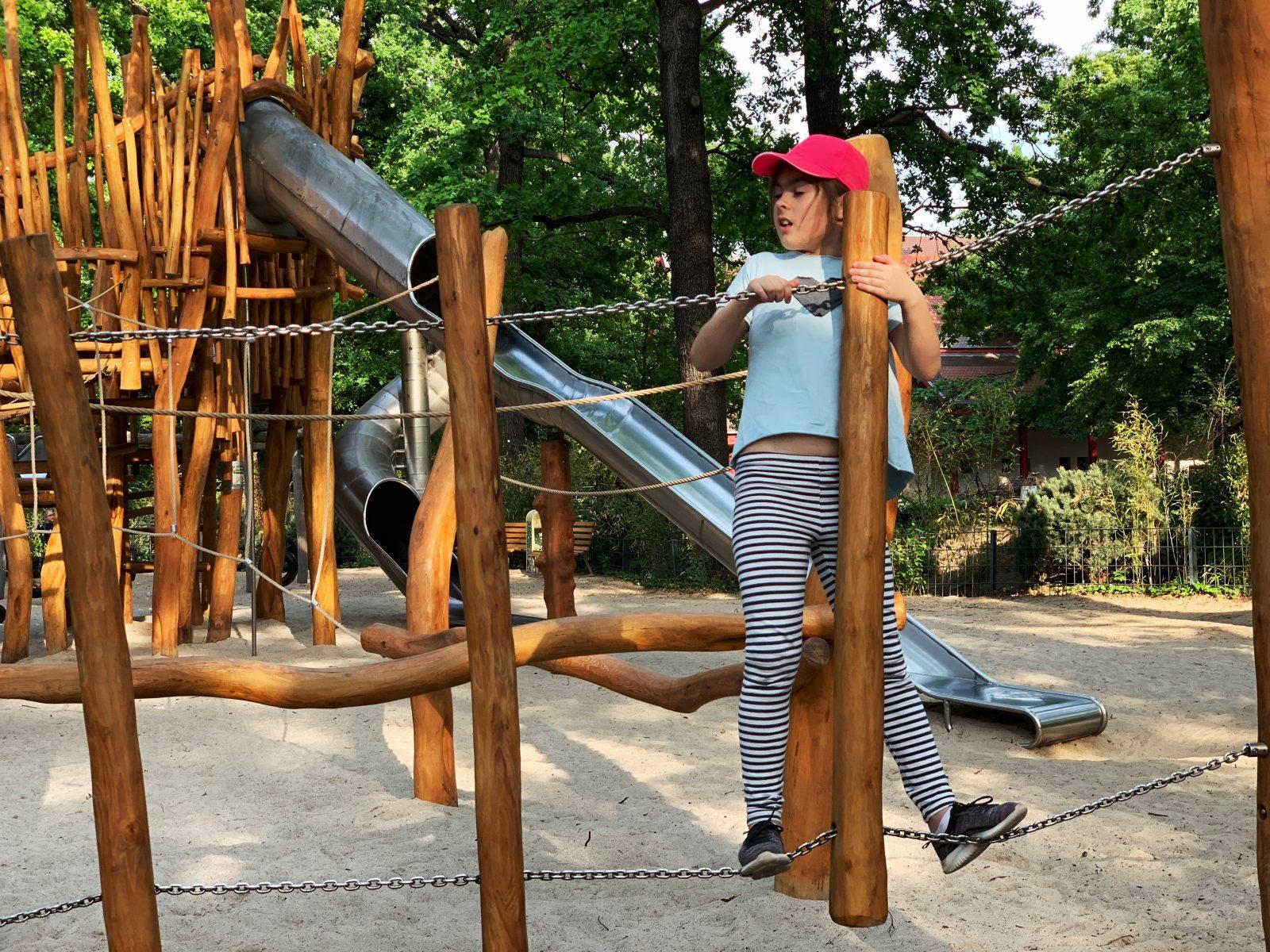 dziewczynka wspina sie na plac zabaw