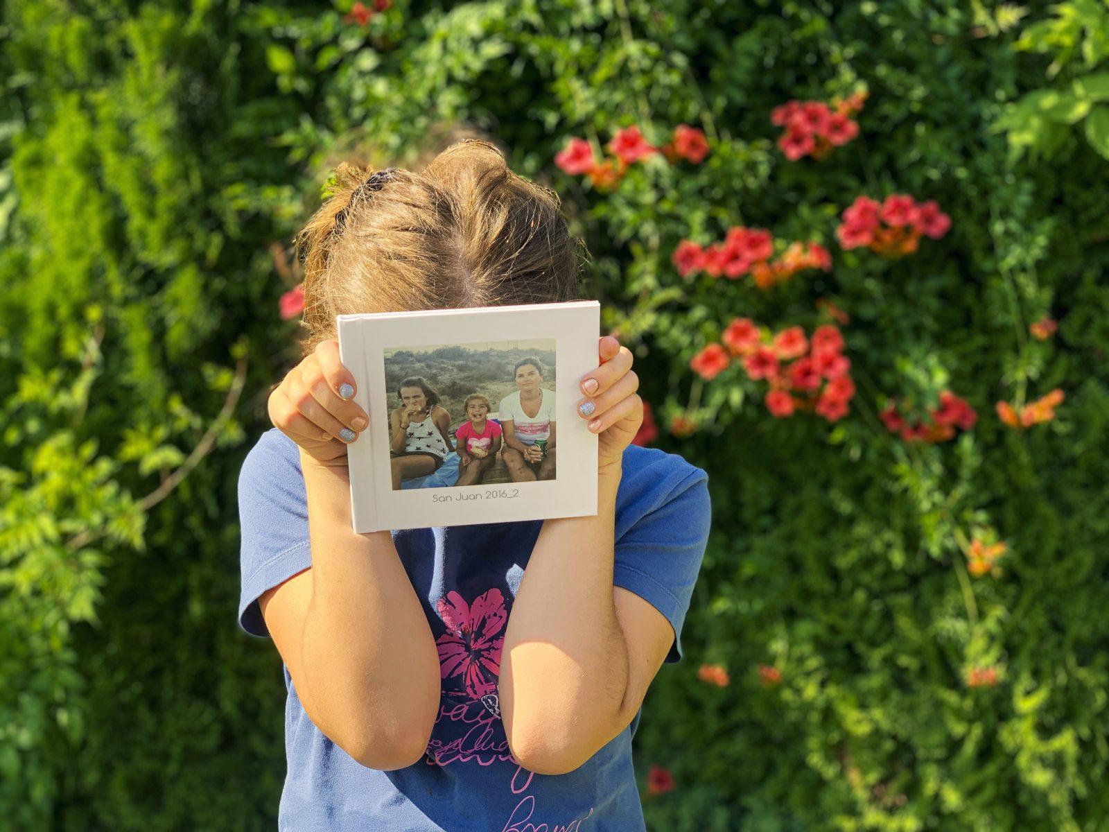 dziewczynka trzyma album ze zdjeciami printu